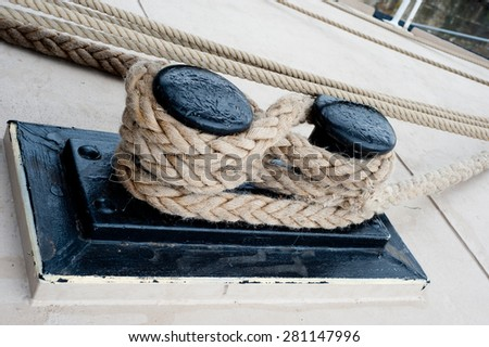Close-up of a mooring rope with a knotted end tied around a cleat - stock photo