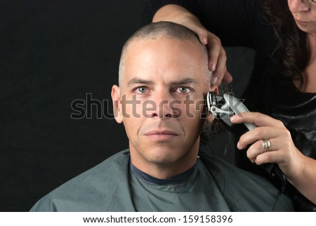 Close-up of a mourning man getting his head shaved. Looking to camera, - stock photo