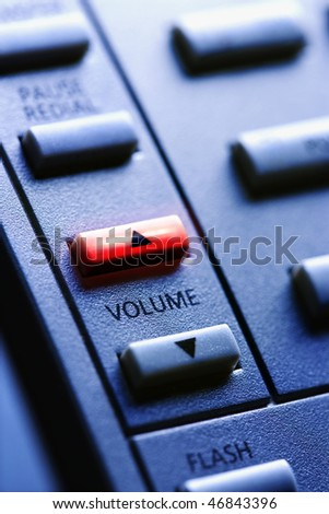 Close up of a multi-line business telephone with lit volume up button. Vertical shot. - stock photo