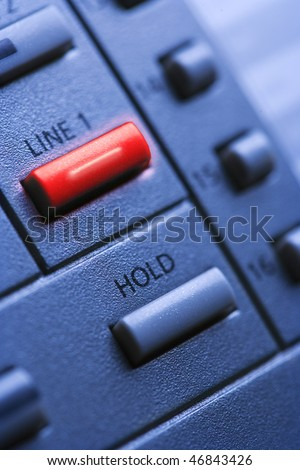 Close up of a multi-line office telephone with lit line one button. Vertical shot. - stock photo