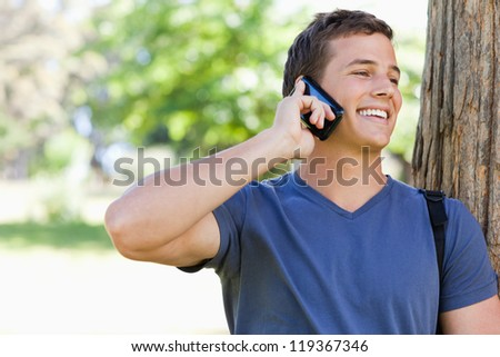 Close-up of a muscled student on the phone in a park - stock photo