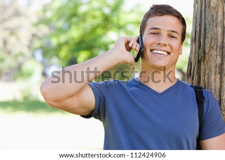 Close-up of a muscled young man on the phone in a park - stock photo
