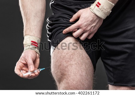 Close up of a muscular man injecting himself with steroids. - stock photo