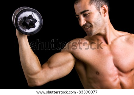 Close up of a muscular young man lifting dumbbells on black background. - stock photo