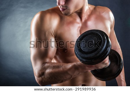 Close Up of a muscular young man lifting weights on dark background - stock photo