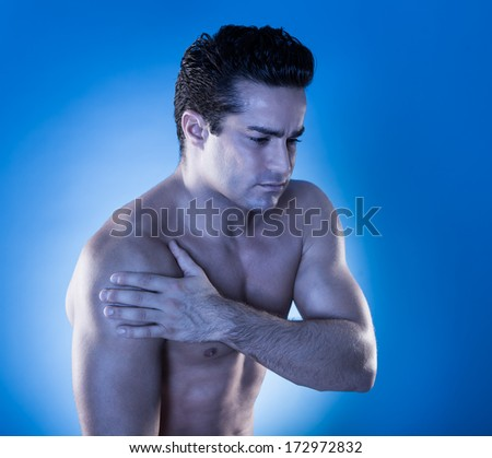 Close-up Of A Muscular Young Man Suffering From Shoulder Pain - stock photo