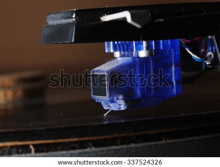 close up of a new style modern technology blue transparent plastic body cover of moving coil pickup and needle for analog vinyl disk installed on vintage retro direct drive turntable play jazz music - stock photo