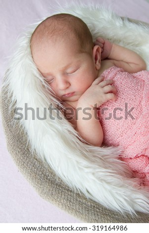 Close up of a newborn baby girl, 7 days old, sleeping on soft fluffy blanket