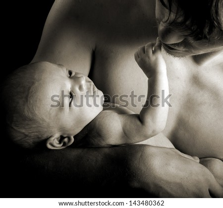 Close up of a newborn touching his fathers face in monochrome with sepia toning - stock photo