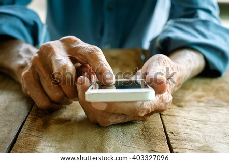 Close up of a old man using mobile smart phone  - stock photo