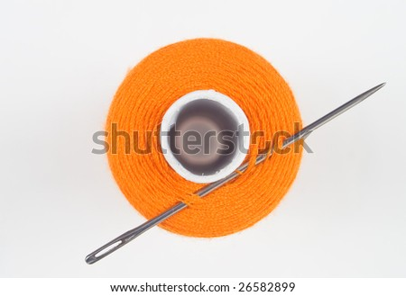close up of a orange sewing spool with needle