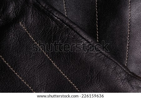 Close up of a pair of black leather gloves, one on top of the other, showing detail