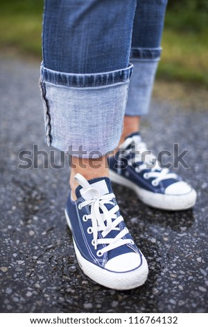 Close up of a pair of blue sneakers and blue jeans on a wet ground - stock photo