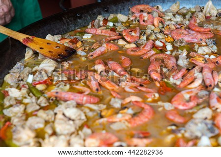 Close-up of a pan with an Spanish paella, a rice dish originally from Valencia, usually garnished with vegetables, saffron and see food. Shallow depth of field. - stock photo