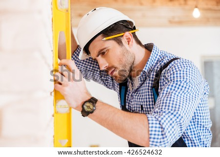 Close-up of a pensive worker checking the yellow level on the concrete wall indoors