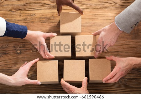 Close-up Of A People Arranging Block On Pyramid Over The Wooden Table