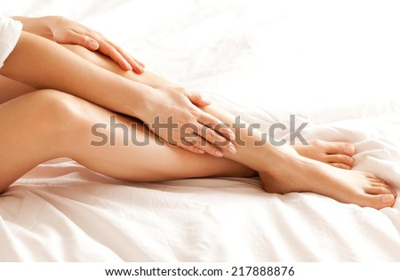 Close up of a perfect female legs. Woman applying moisturizer. - stock photo