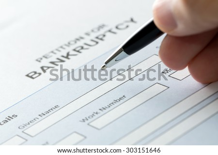 Close up of a person filling petition of bankruptcy form