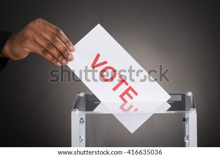 Close-up Of A Person Hand Putting Vote In A Ballot Box Against Gray Background - stock photo