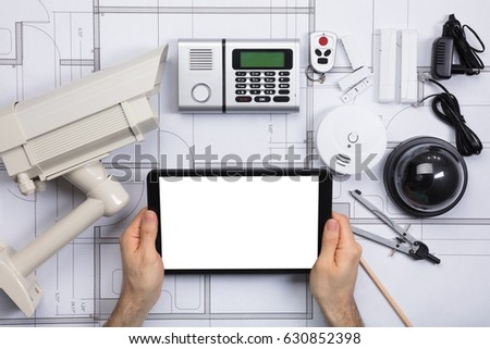 Closeup person holding blank screen digital stock photo 630852398 close up of a person holding blank screen digital tablet on blueprint with security equipments malvernweather