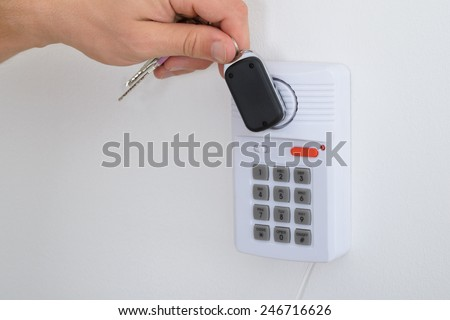 Close-up Of A Person Holding House Keys Arming A Security System - stock photo