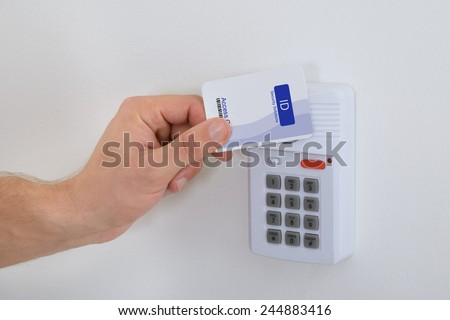 Close-up Of A Person Holding Security Card To Open Door - stock photo