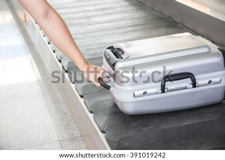 Close-up of a person holding suitcase on conveyor belt. - stock photo