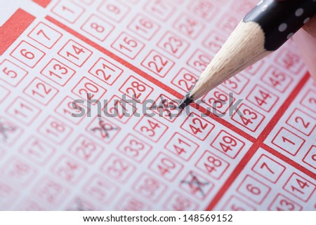 Close-up Of A Person Marking Number On Lottery Ticket With Pencil - stock photo