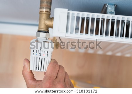Close-up Of A Person's Hand Adjusting Temperature Of Radiator Thermostat - stock photo