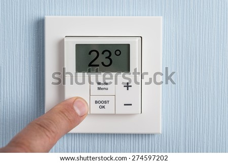 Close-up Of A Person's Hand Adjusting Thermostat - stock photo
