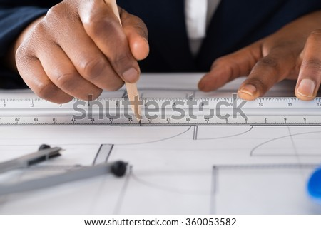 Close-up Of A Person's Hand Drawing Blue Print With Pencil - stock photo