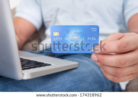 Close-up Of A Person's Hand Showing Credit Card While Using Laptop - stock photo
