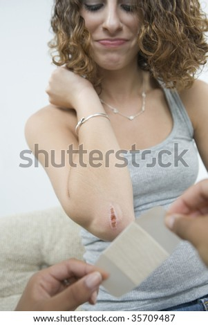 Close-up of a person's hands putting a bandage on a teenage girl's wounded elbow