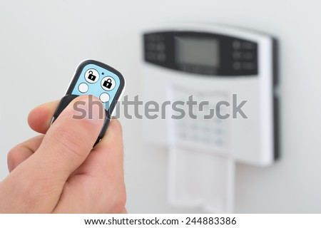 Close-up Of A Person Using Remote Control To Disarm The Security System - stock photo