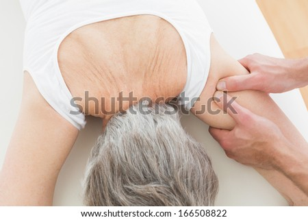 Close-up of a physiotherapist massaging a senior woman's arm in the medical office - stock photo