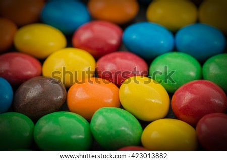 Close up of a pile of colorful chocolate coated candy. Selective focus on foreground.