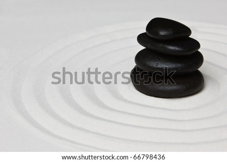Close-up of a pile of stones on raked sand in a Japanese ornamental or zen garden. - stock photo