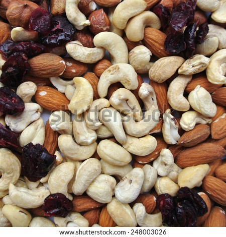 Close-up of a pile of various nuts - almonds, cashews and hazelnuts, and dried cranberries.  - stock photo