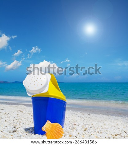 close up of a plastic watering can and shell by the shore - stock photo