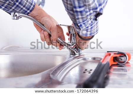 Close-up Of A Plumber Fixing Washbasin With Wrench - stock photo