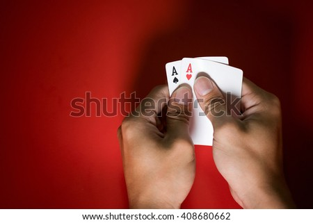 Close up of a poker player holding playing cards on red table.