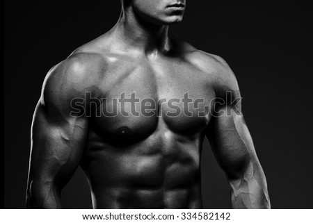 Close-up of a power fitness man. Strong and handsome young man with muscles and biceps. Studio shooting on black background.