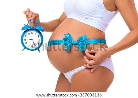Close-up of a pregnant belly with a blue ribbon and an alarm clock. Concept of pregnancy - stock photo
