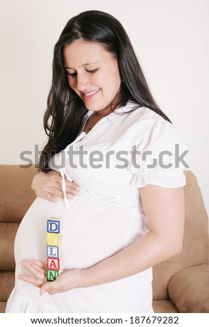 Close up of a pregnant woman with baby letters on her hand - stock photo