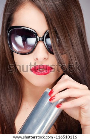 Close up of a pretty woman with sun glasses holding can
