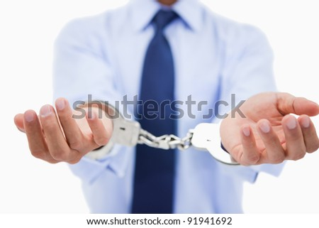 Close up of a professional's hands with handcuffs against a white background - stock photo
