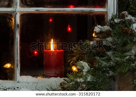 Close up of a red candle, selective focus on flame and top part of candle, glowing in window with pine tree and snow outside. Christmas concept. - stock photo