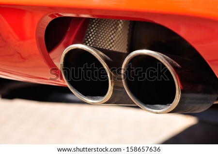 Close up of a red car dual exhaust pipe - stock photo