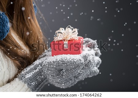 Close-up of a red giftbox in female hands in knitted mittens  - stock photo