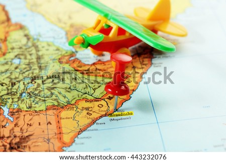 Close-up of a red pushpin on a map of Mogadishu, Somalia Africa and airplane toy - travel concept - stock photo